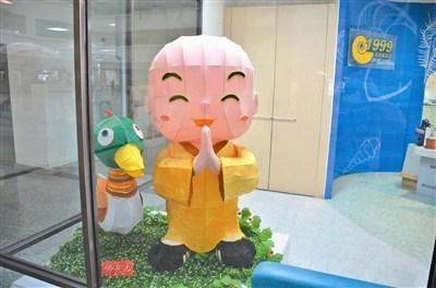 可爱的小沙弥(灯)站在高雄联合服务中心的美术馆内合十祝福.
