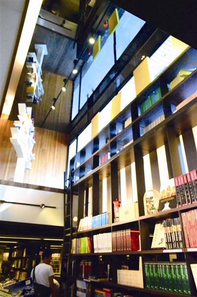 茉莉二手书台中店挑高大片玻璃橱窗里的两棵树型书架,被窗外的蓝天