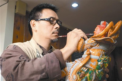 柯锦中专注的用漆线记忆为木雕神像上色.图/赖香珊