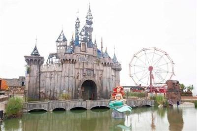 废弃露天泳池康纳打造了一个名为dismaland的乐园,不仅名称恶搞迪士尼